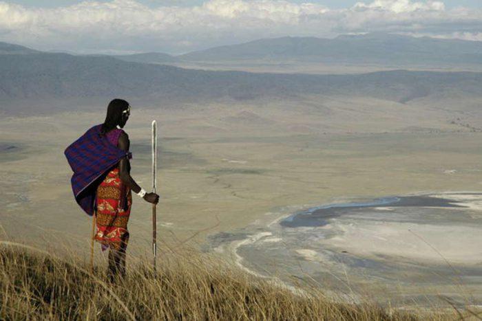 Masaai krijger kijkt over de Ngorongoro krater